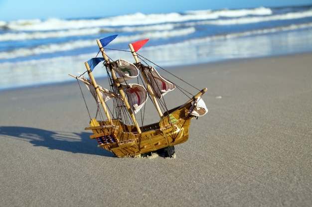 Barco de juguete en la orilla del mar