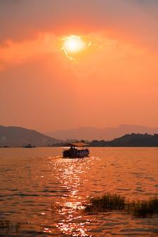 Barco en el lago pichola en puesta de sol. udaipur, rajasthan, india