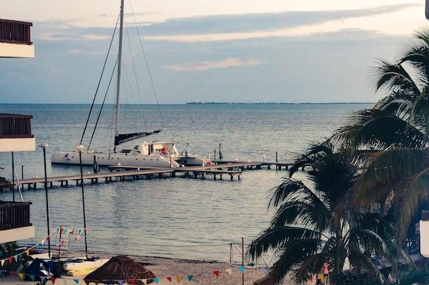 Barco de lujo por un muelle en el hermoso océano cerca de la playa