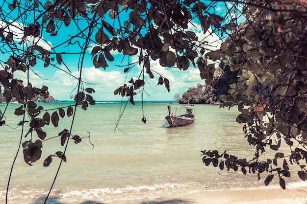 Barco de madera de cola larga en la orilla con una playa de arena en la península de railay