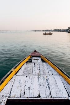 Barco de madera navegando en el río ganges en varanasi, india