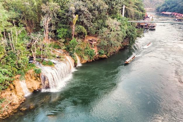 Barco de madera que navega por el río kwai con cascada en la selva tropical