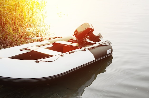 Barco de motor inflable en el agua cerca de la costa al amanecer o al atardecer, en el exterior. aguas tranquilas, enfoque selectivo en el motor del barco. concepto de pesca, paseos en barco.