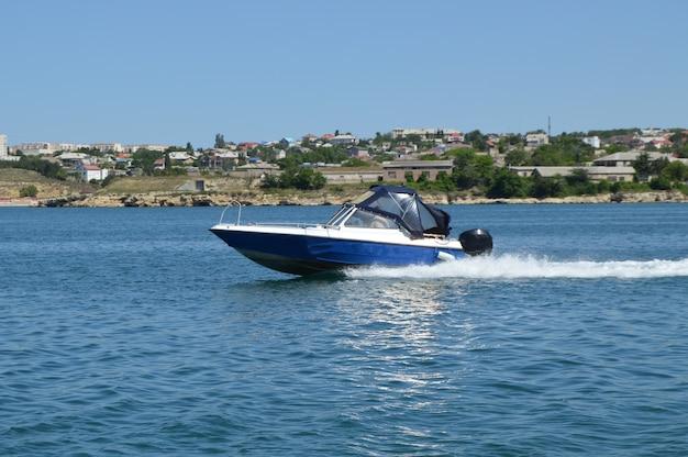 Barco a motor se mueve a lo largo del mar a lo largo de la costa, dejando un rastro