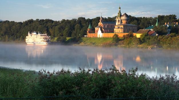 Un barco de motor turístico con el telón de fondo del monasterio masculino nikolsky en staraya ladoga en la región de leningrado en una mañana brumosa en el río volkhov. viajando por los ríos de rusia