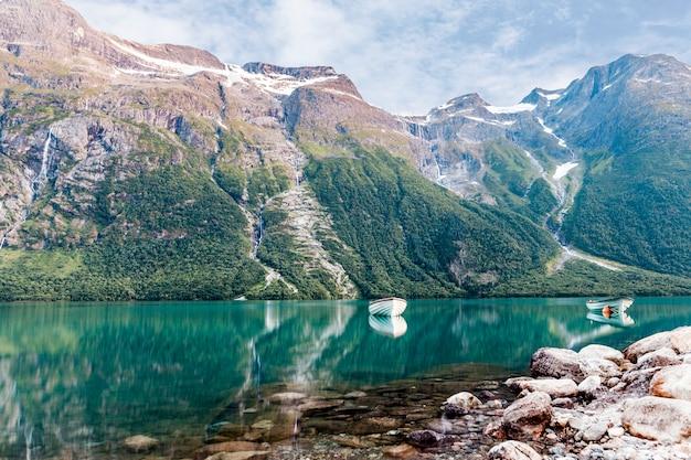 Un barco náutico vacío en el idílico lago cerca de la montaña de roca
