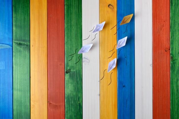 Barco de origami hecho de papel amarillo liderando a los demás en una imagen conceptual.