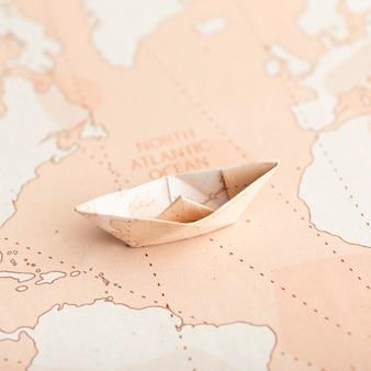 Barco de origami pequeño de ángulo alto en el mapa