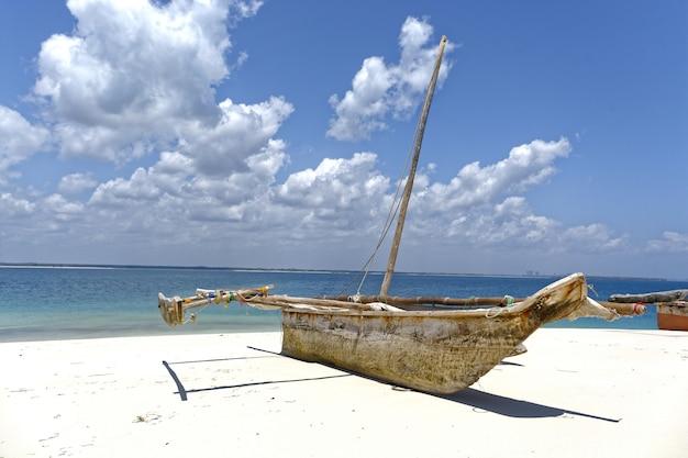 Barco en la orilla cerca del mar en un día soleado con cielo nublado en el fondo