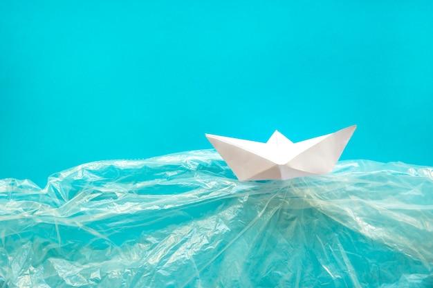 Barco de papel en agua de plástico