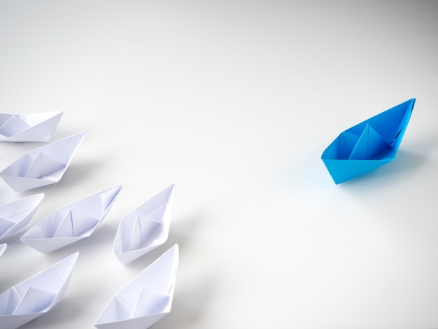 Barco de papel azul líder entre barcos blancos.