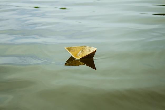 Un barco de papel blanco flotando en el agua