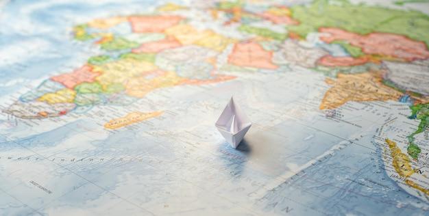 Barco de papel navegando en el océano