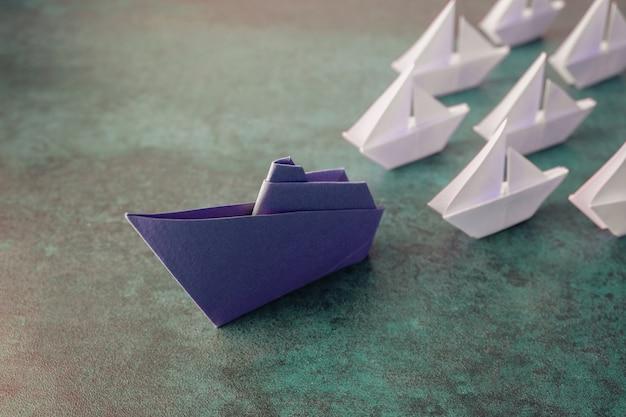 Barco de papel de origami con pequeños veleros