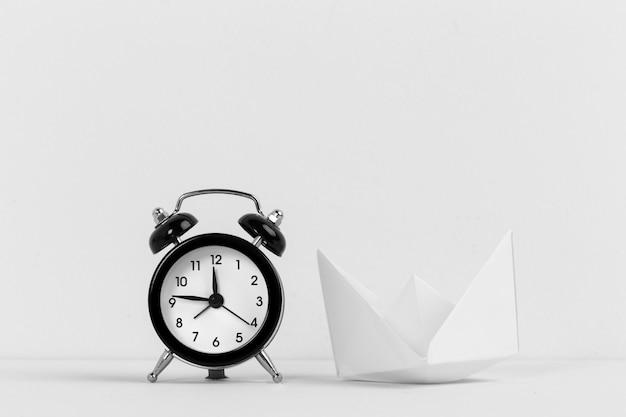 Barco de papel con reloj despertador negro vintage
