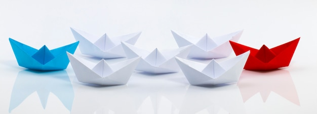 Barco de papel rojo y barco de papel azul liderando entre barcos de papel blanco