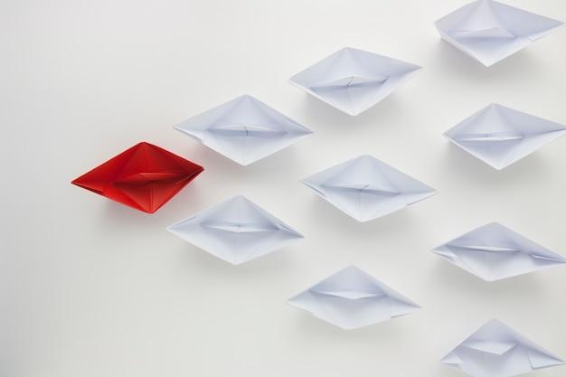 Barco de papel rojo liderando los blancos, concepto de liderazgo.