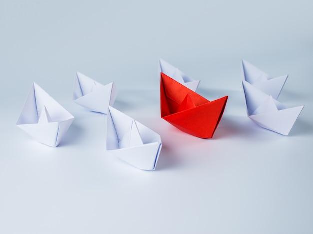 Barco de papel rojo liderando entre blancos
