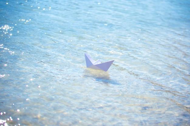 Barco de papel sobre las olas de agua azul.