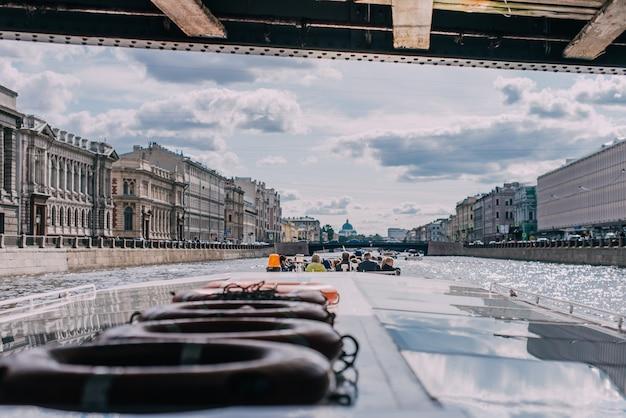 Barco de pasajeros con pasajeros pasa bajo el puente sobre el río fontanka