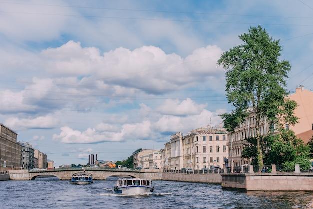 Barco de pasajeros con turistas pasa por el río fontanka