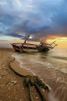 El barco de pesca dañado se encuentra en una costa en pattaya, tailandia.
