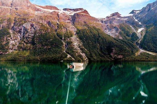 Barco de pesca en un lago inmóvil con altas montañas en fondo