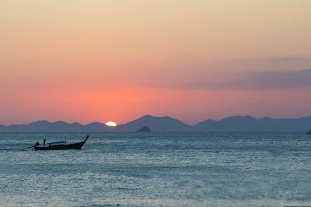 Barco de pesca de madera navegando por el mar con el telón de fondo de la puesta de sol y las montañas