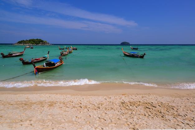 Barco de pesca en la playa de arena del mar en el mar azul y fondo azul en la puesta del sol