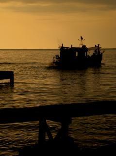Barco de pesca en la puesta del sol de oro