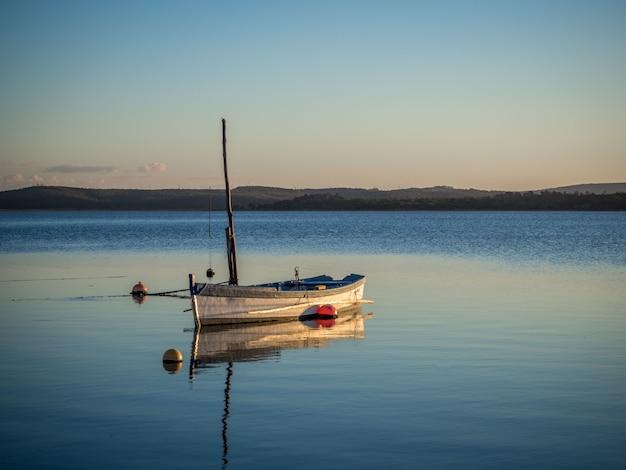 Barco de pesca en el río con la hermosa puesta de sol de fondo
