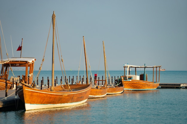 Barco de pesca tradicional atracado en un atracadero largo con tranquilas aguas azules.