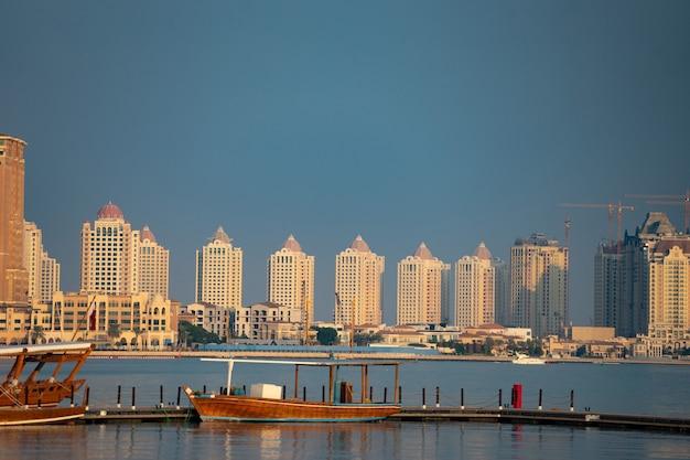 Barco de pesca tradicional en atracado con la ciudad en largo atracadero con tranquilas aguas azules.