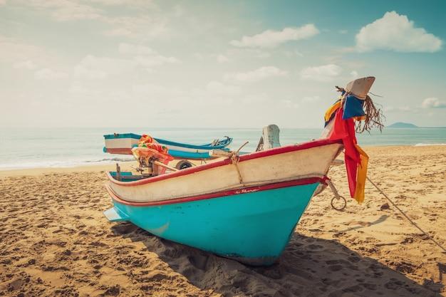 Barco de pesca de la vendimia en la playa al atardecer con el cielo y el mar en el fondo.