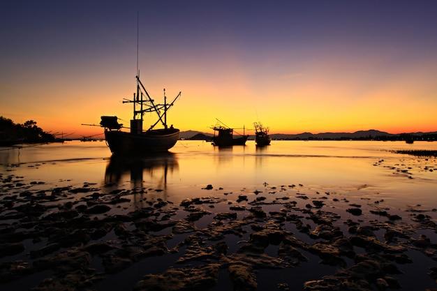 Barco de pescadores navega de regreso en la puesta de sol