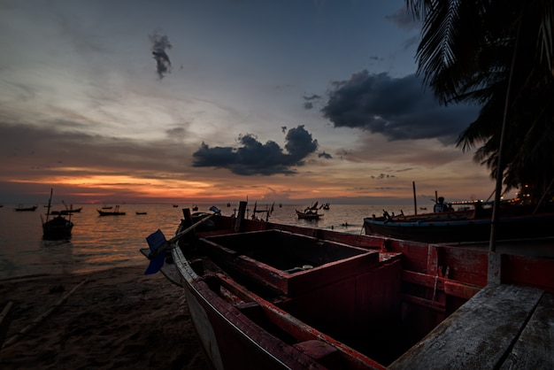 El barco de los pescadores en la playa con el cielo del atardecer.