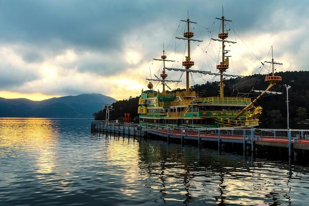 Barco pirata de visita y puerta roja de torii en el lago ashi en la puesta del sol, hakone, japón