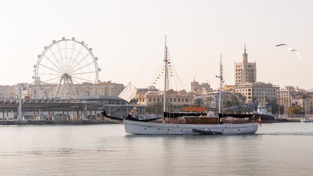 Barco que cruza el puerto de málaga con la noria al fondo.