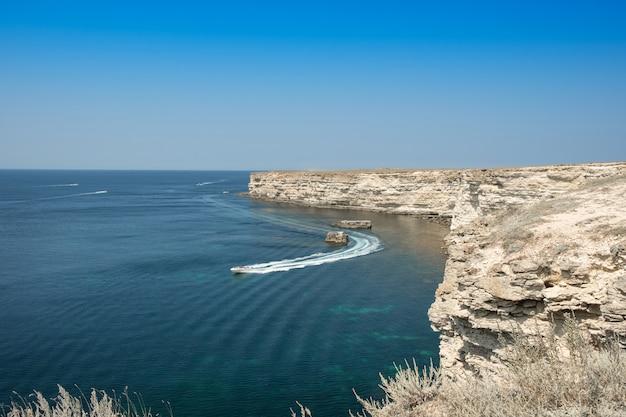 Barco que navega a la hermosa costa rocosa en un día soleado