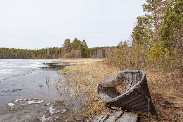 Barco roto viejo en la costa del río en un día nublado.