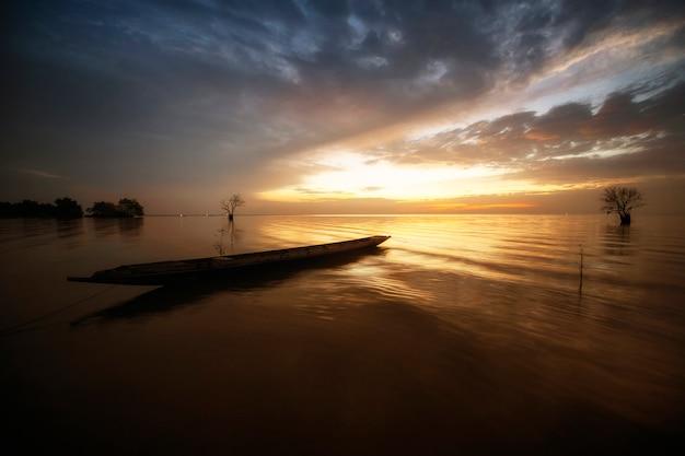 Barco tailandés de la cola larga y salida del sol hermosa en el mar por mañana.