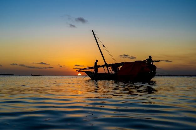 Barco tradicional dhow de pescadores durante la puesta de sol en el océano índico en la isla de zanzíbar, tanzania, áfrica oriental