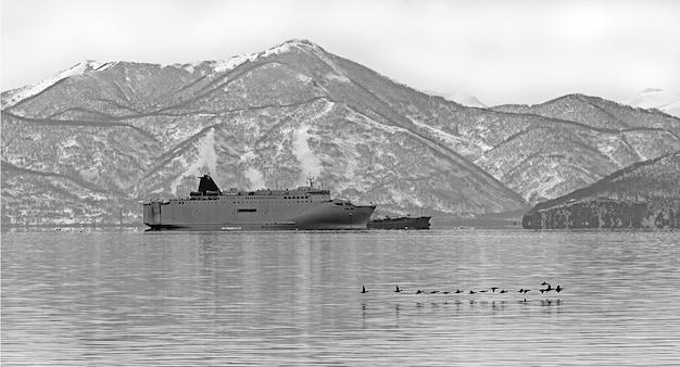 Barco de transporte militar en la bahía de invierno en un día nublado frente a colinas cubiertas de nieve