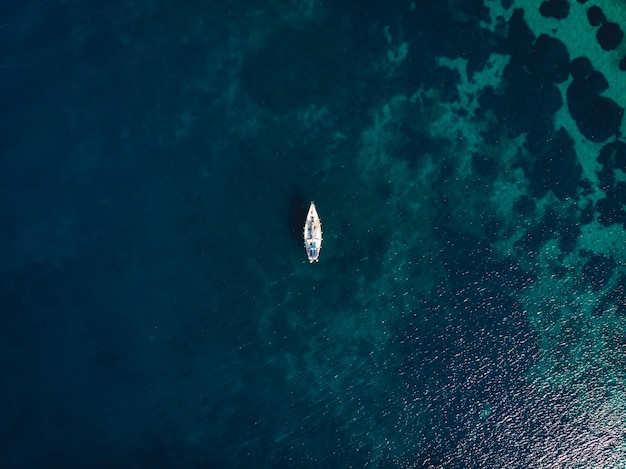 Barco único en medio del mar azul claro