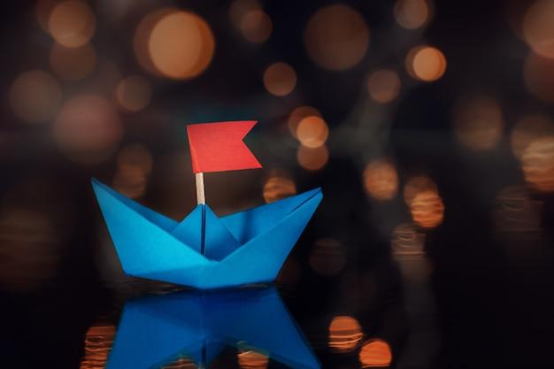 Barco de vela de papel azul en la oscuridad