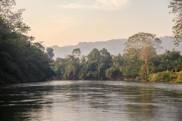 Barco de vela de turismo de selva tropical en el río kwai