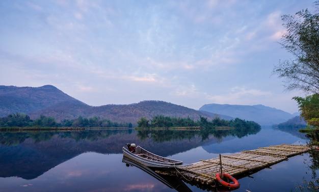 Los barcos atracaron en un lago y una reflexión de la montaña. lago natural de la presa en bosque.