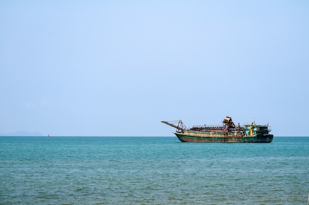 Barcos a la deriva de arena flotando en la línea de horizo en el mar