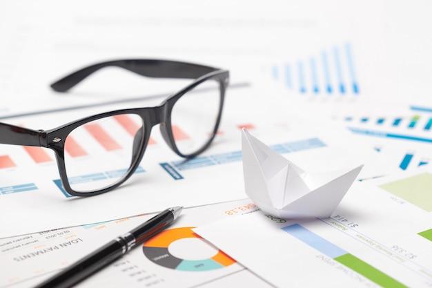 Barcos hechos de papel gráfico en cuaderno con gafas y pluma