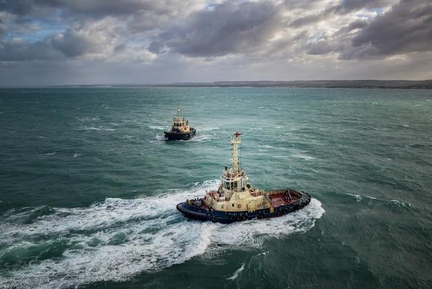 Barcos de investigación navegando en el océano turquesa bajo el cielo nublado